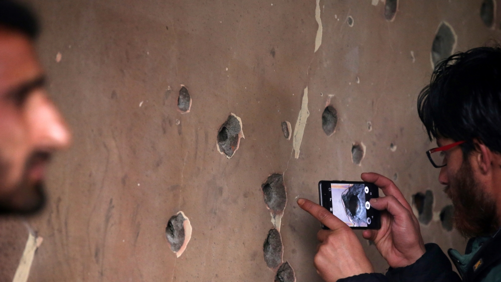 A man uses his mobile phone to take pictures of a bullet-riddled wall of a residential house that was damaged during a gun battle between Zakir Rashid Bhat and Indian security forces