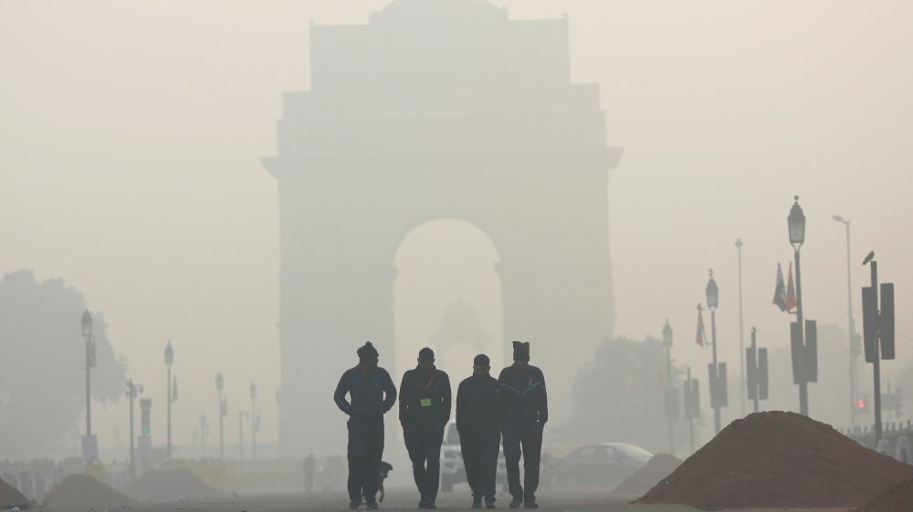 Men walk in front of the India Gate shrouded in smog in New Delhi