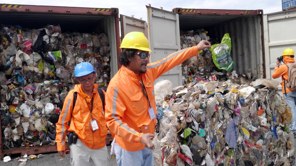Philippine customs officials inspect cargo containers containing tonnes of garbage shipped by Canada at Manila port
