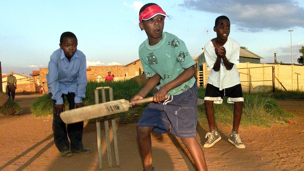 Lesego Chauke waits for the ball as he bats in front of wicketkeeper Tebogo Mashila and fielder Buti Phadima, as they play cricket after school in one of the black township in Tsakane Brakpan, east of