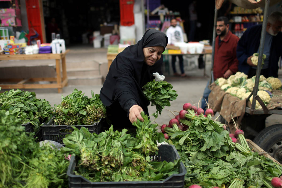 A Palestinian woman sells vegetables in the southern Gaza Strip. [Ibraheem Abu Mustafa/Reuters]