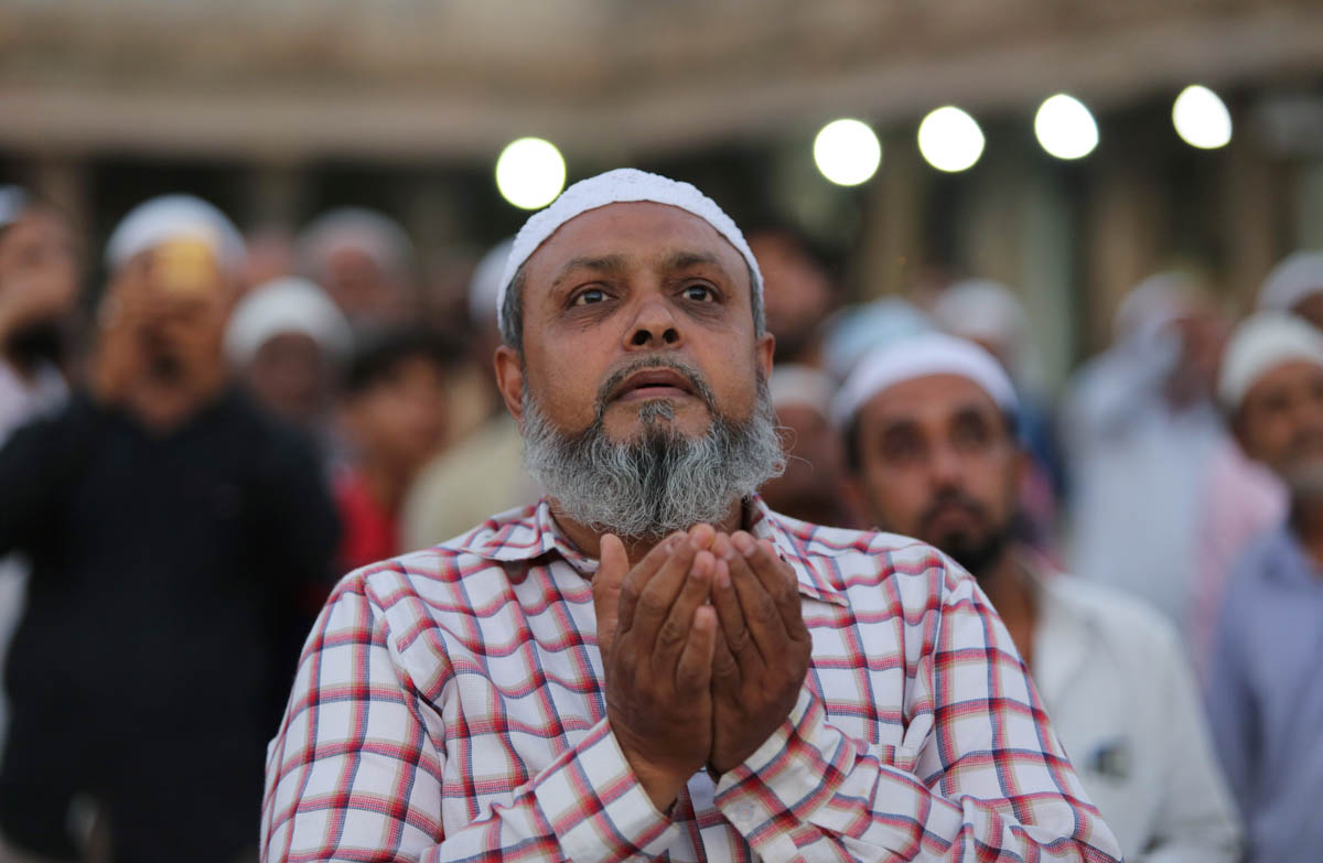 A Muslim man prays as he and others assemble to spot the crescent moon, on the eve of the holy month, at a mosque in Ahmedabad, India. [Amit Dave/Reuters]