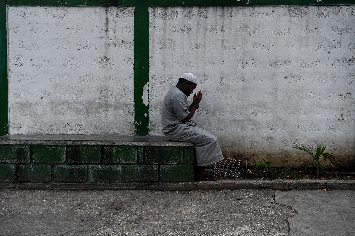 A Muslim man offers prayers before iftar, the meal after sunset, at the Masjid At-Tawheed mosque in Port-au-Prince, Haiti. Muslims fast from dawn to dusk until Eid celebrations mark the end of the holy month. [Chandan Khanna/AFP]