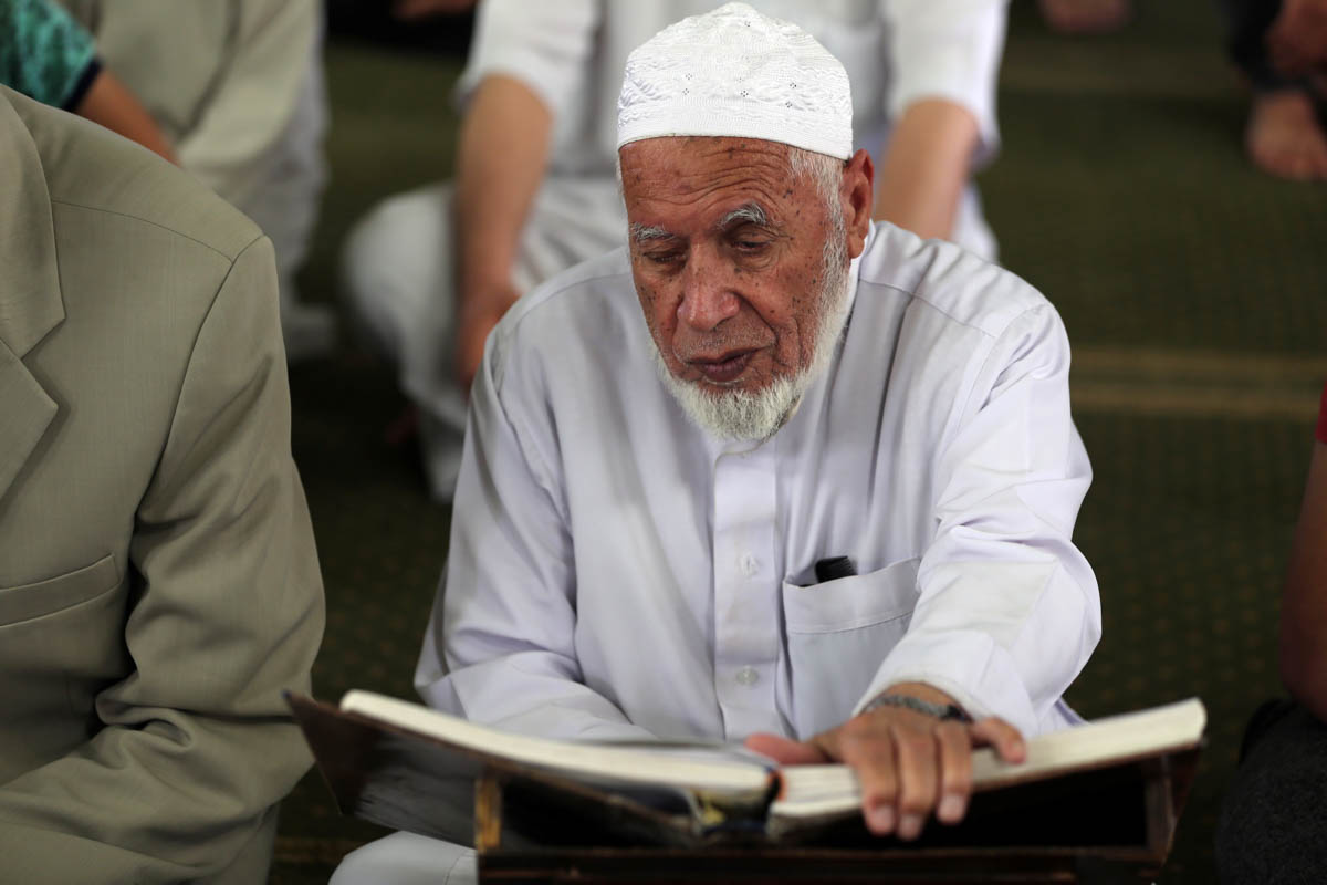 A Palestinian man reads the Quran in a mosque in the southern Gaza Strip. [Ibraheem Abu Mustafa/Reuters]