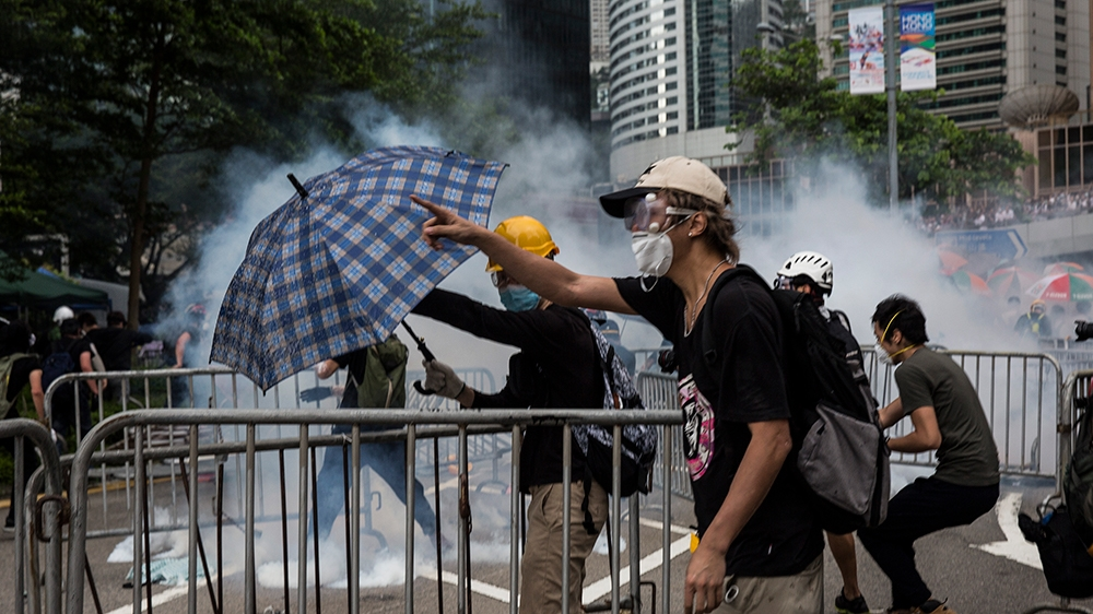 Protesters wearing masks reacts after police fired tear gas during demonstrations outside the Legislative Council Complex in Hong Kong on June 12, 2019. - Violent clashes broke out in Hong Kong on Jun