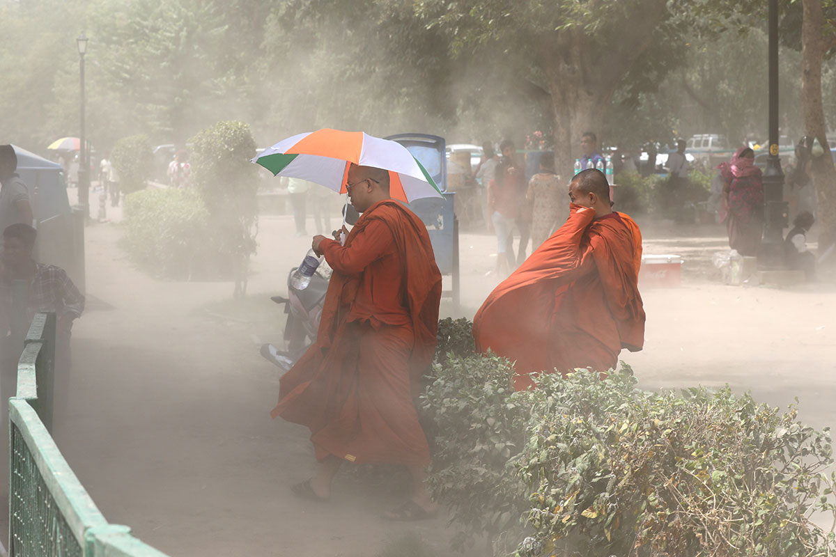 Monks protect themselves during hot weather in New Delhi, India.  Temperatures rose to as high as 50.8 Celsius on some days. [Rajat Gupta/EPA]