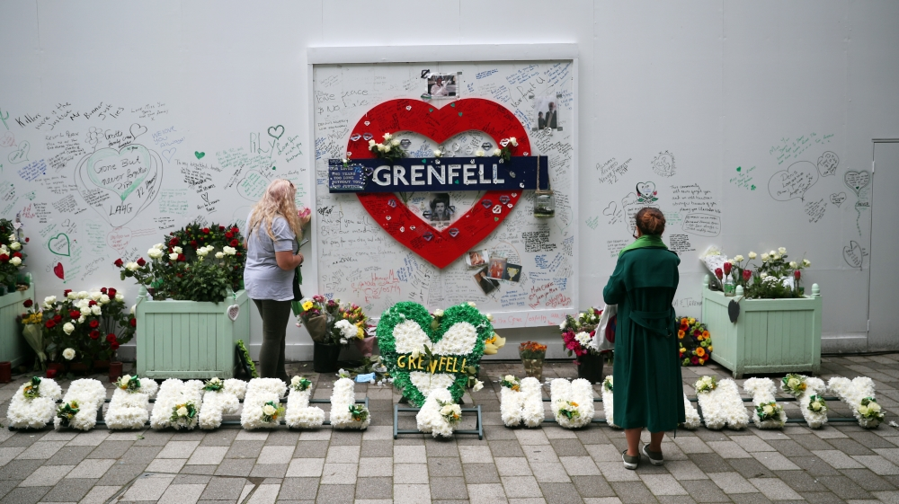 Women looks at a hoarding covered in messages of condolence at the base of Grenfell tower two years after the fire in London