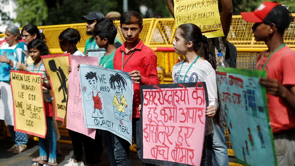 Children hold placards during a protest against the deaths of children who have died this month from encephalitis, commonly known as brain fever, in the eastern Indian state of Bihar, in New Delhi, In