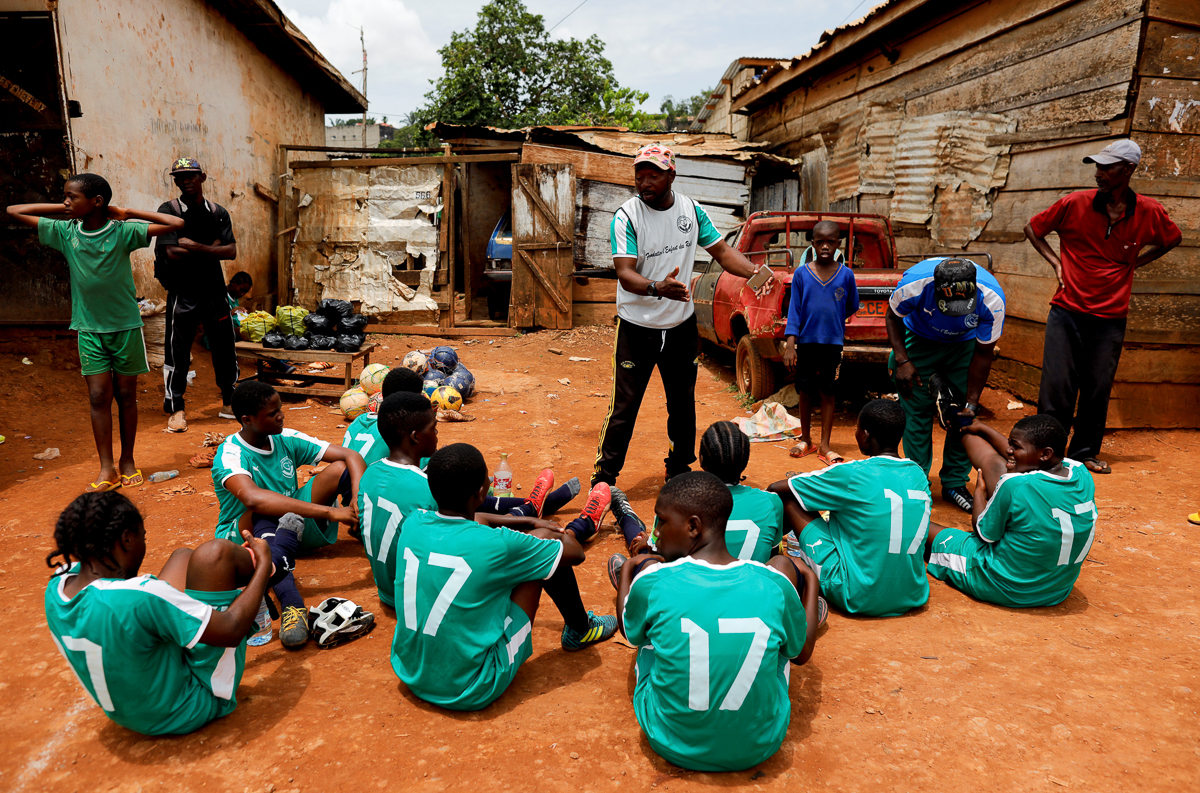 Emmanuel Eteme Biolo, a girls' U17 team coach, talks with his team during half-time of a match at the Rails Foot Academy field in Yaounde. The academy currently trains around 70 girls, most of whom come from poor backgrounds and would otherwise not be able to afford even their own football boots. [Zohra Bensemra/Reuters]