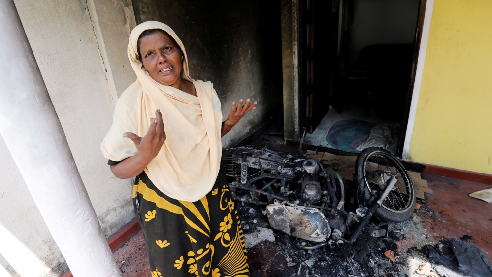 A Muslim woman reacts next to a burnt motorbike and her house after a mob attack in Kottampitiya