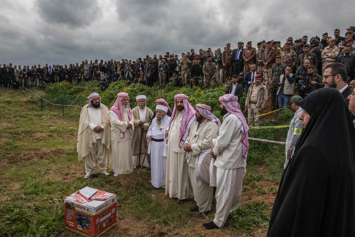The Yazidi spiritual leader, Sheikh Kato together with other clerics, celebrate the opening of the first mass grave in Kojo, Sinjar, by releasing white doves from a box. Survivors and families of victims of the genocide gathered on this day. Around 70 mass graves are to be excavated for the exhumation of the bodies in Sinjar. [Alessio Mamo/Al Jazeera]
