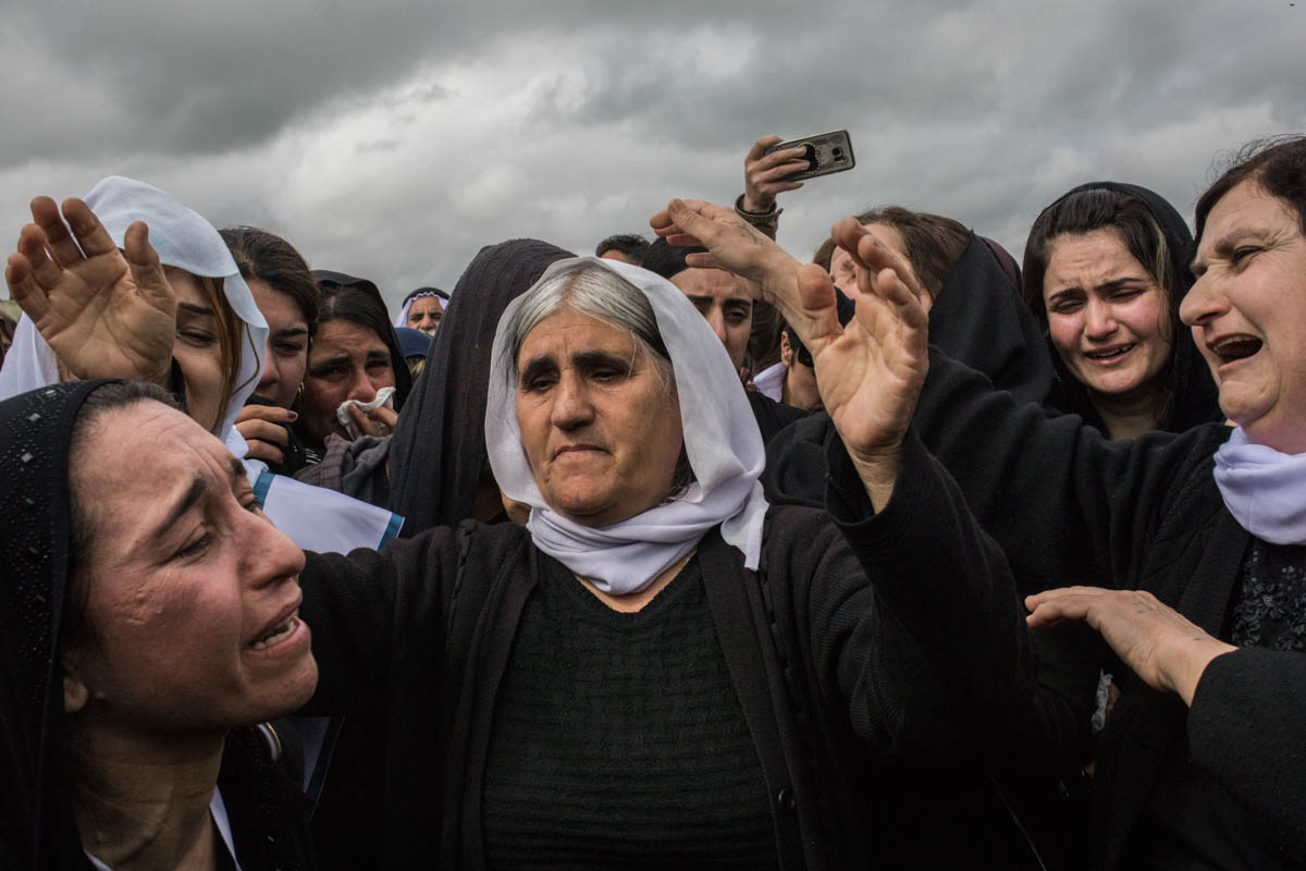 Yazidi women of different ages cry during the ceremony marking of the opening of the mass graves in Kojo, Sinjar. They are the mothers, sisters, wives of the hundreds of men killed by ISIL in 2014 in what the UN said amounted to genocide. [Alessio Mamo/Al Jazeera]