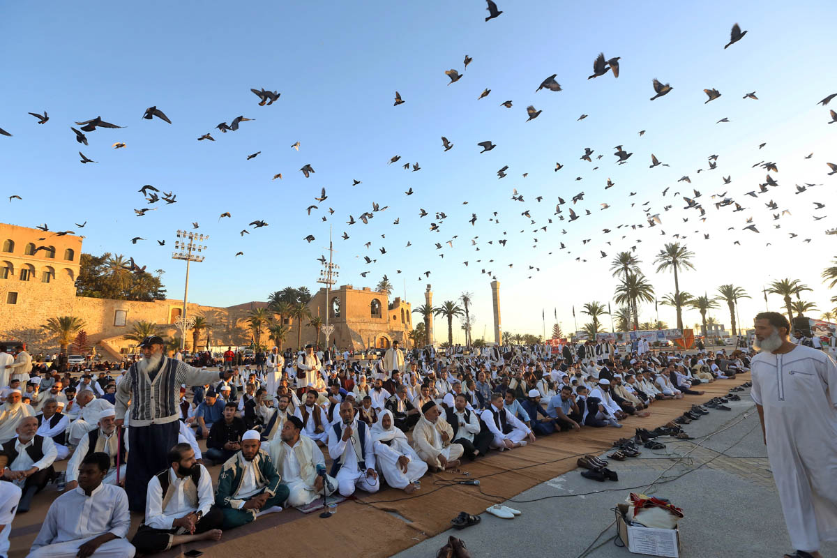 Libyan Muslim worshippers gather to perform Eid al-Fitr prayers at the Martyrs Square in the capital Tripoli. [Mahmud Turkia/AFP]