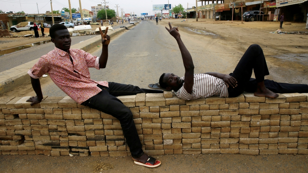 Sudanese protesters rest on bricks used to barricade a street, demanding that the country's Transitional Military Council handover power to civilians, in Khartoum