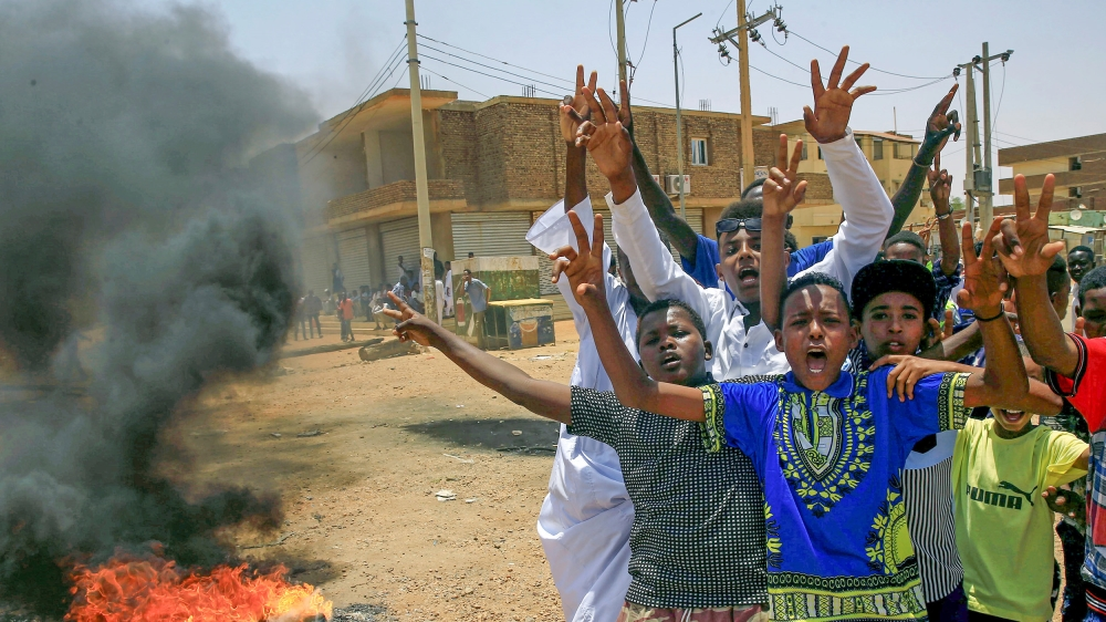 Sudanese protesters gesture and chant slogans at a barricade along a street, demanding that the country's Transitional Military Council hand over power to civilians, in Khartoum, Sudan June 5, 2019. R