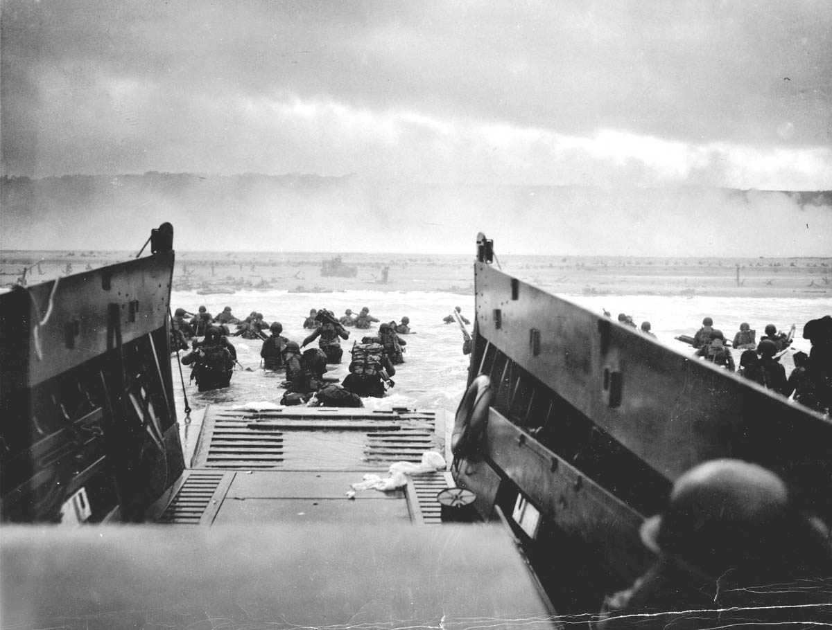 US troops wade ashore from a Coast Guard landing craft at Omaha Beach during the Normandy D-Day landings near Vierville-sur-Mer, France, on June 6, 1944. [Robert F Sargent/US National Archives/Reuters]