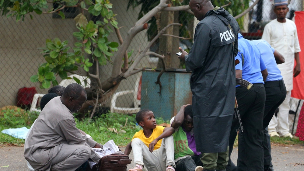 Police officers approach a man in Abuja