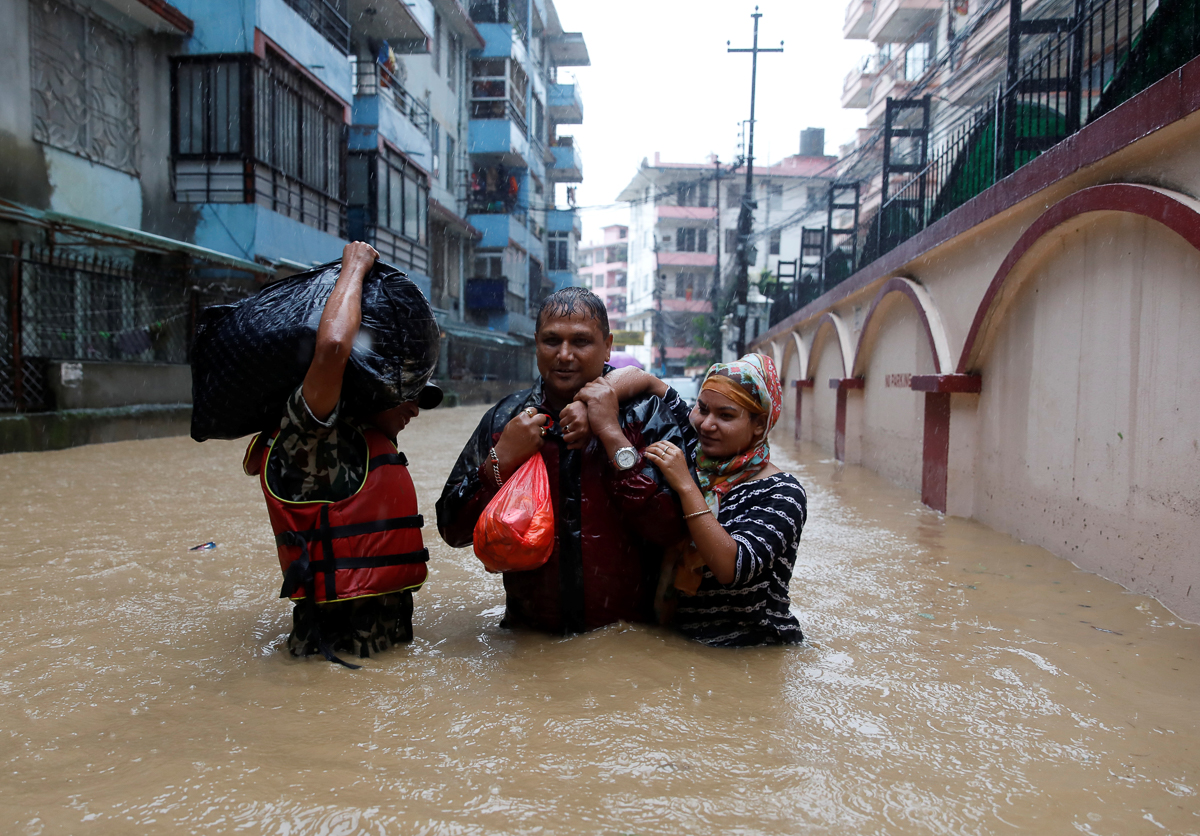 Residents of Kathmandu walk towards dry ground from a flooded colony. [Navesh Chitrakar/Reuters]