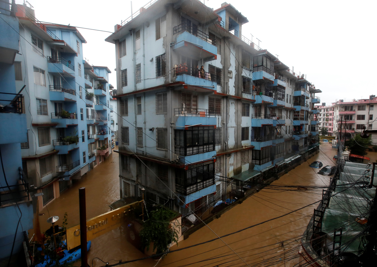 Residents look from a balcony to a flooded neighbourhood in Kathmandu. [Navesh Chitrakar/Reuters]