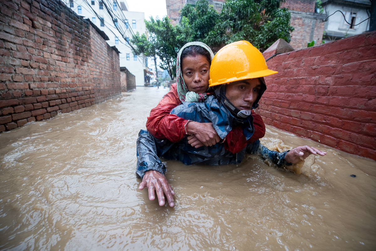 An emergency responder carries a woman from flooded houses in Kathmandu. [Narendra Shrestha/EPA]