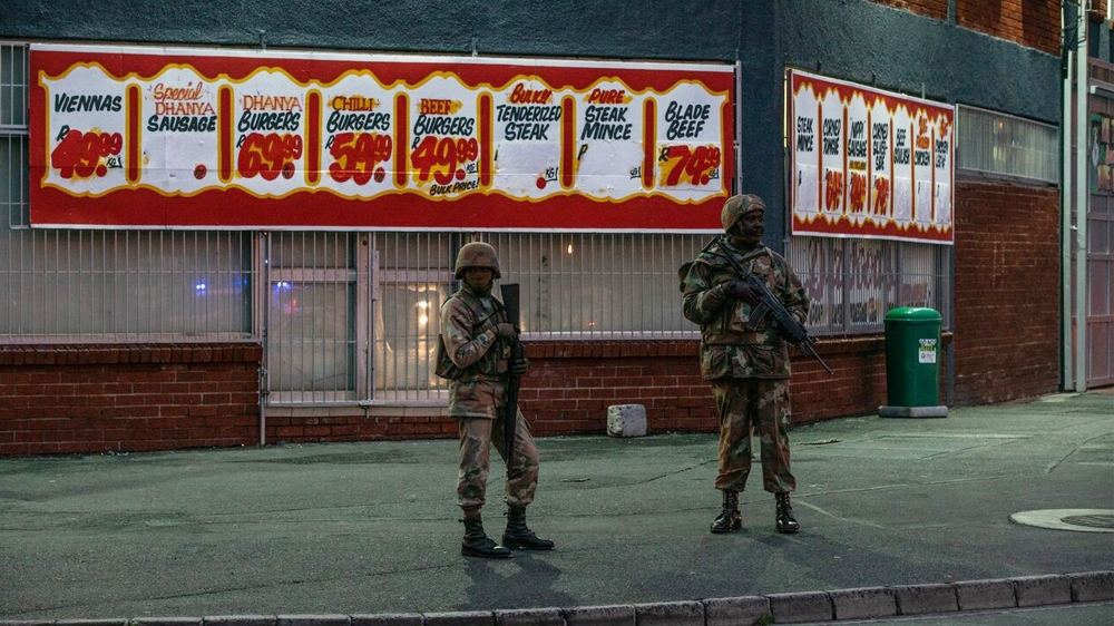 Soldiers stand in front of a shop  in Hanover Park, in a heavily gang-afflicted area on the Cape Flats [Shaun Swingler/Al Jazeera]