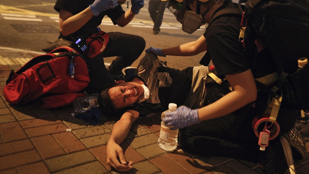 Medical workers help a protester in pain from a tear on a street in Hong Kong, Hong Kong. July 21, 2019. Hong Kong police have thrown tear canisters at protesters after they refu