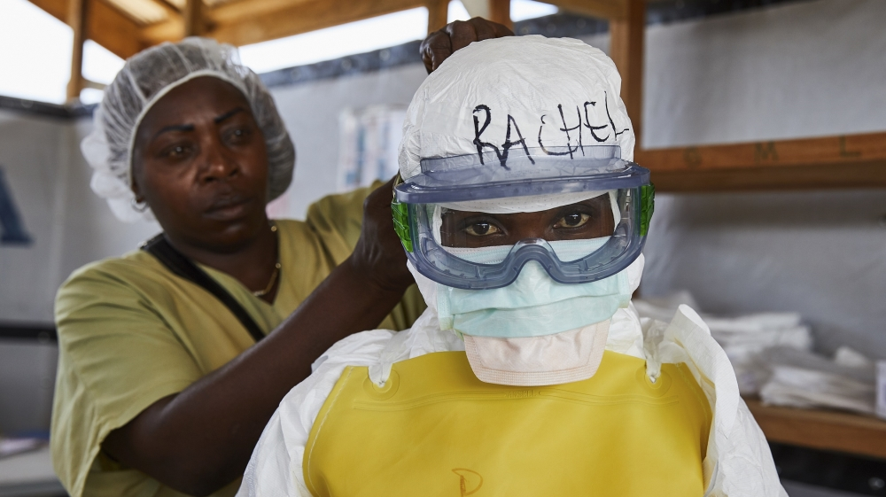 A health worker gets dressed in protective medical garments at an Ebola transit centre in Beni in North Kivu province