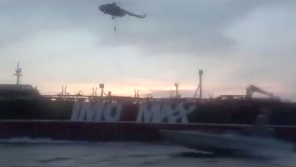 An Iranian Revolutionary Guard troop member rapels to British-flagged tanker Stena Impero's deck from a helicopter near the strait of Hormuz