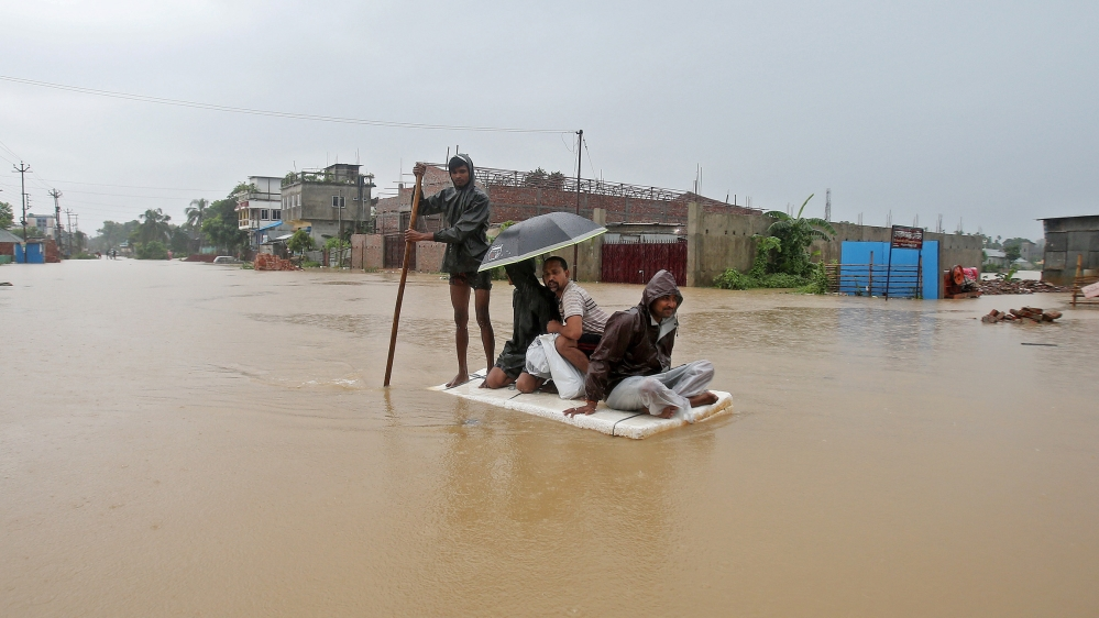 Villagers use a makeshift raft to cross a flooded area on the outskirts of Agartala, India, July 15. REUTERS/Jayanta Dey