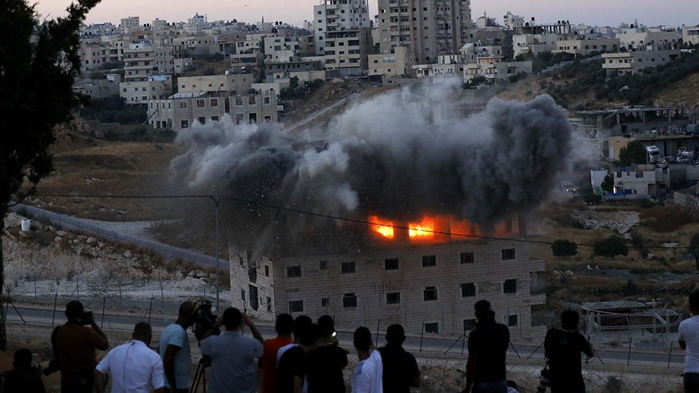 A Palestinian building is blown up by Israeli forces in the village of Sur Baher which sits on both sides of the Israeli barrier in East Jerusalem and the Israeli-occupied West Bank, 22 July 2019. Isr