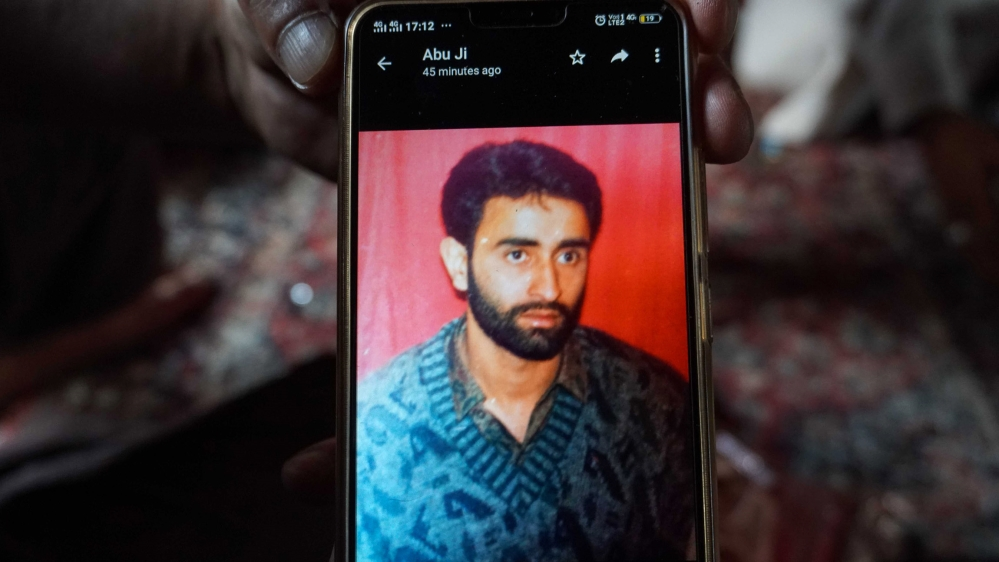 Bhat's brother shows his picture of 1996 on phone the year when he was arrested. [Rifat Fareed/Al Jazeera]