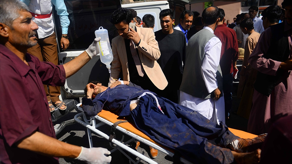 Graphic content / An injured Afghan man is transported on a stretcher after being injured when a bus hit a roadside bomb on the Kandahar-Herat highway, at a hospital in Herat on July 31, 2019. - Dozen