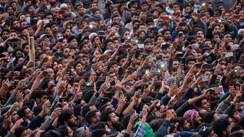 People use their mobile phones to take photographs of the body of Kashmiri professor Mohammad Rafi Bhat, a suspected militant, after he was killed in a gunbattle with Indian security forces in south K