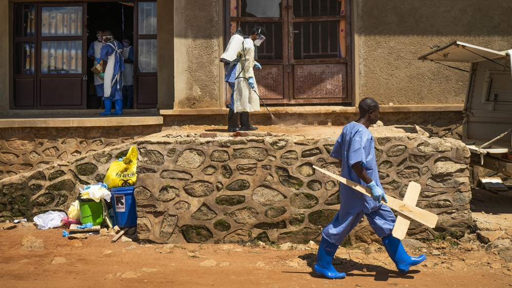 A morgue employee walks with a cross past others disinfecting the entrance to the morgue in Beni, Congo DRC [File:Jerome Delay/AP Photo]