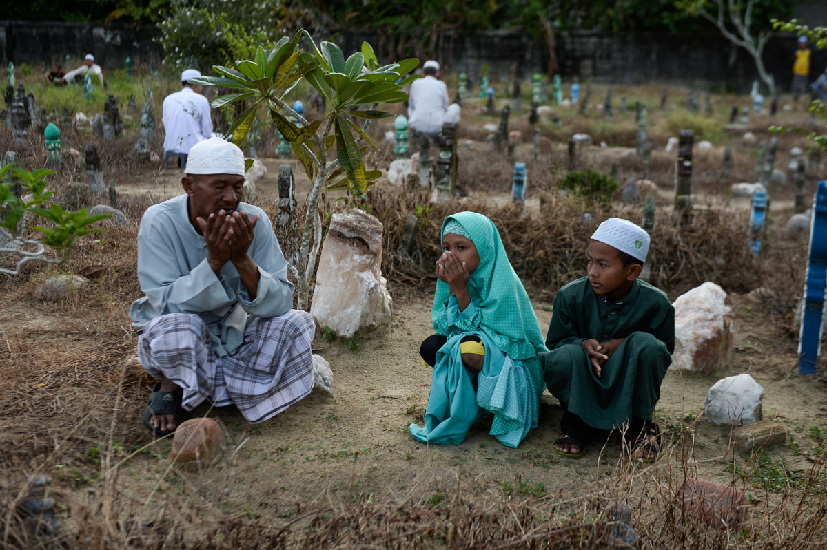 Thai Muslims pray at the tomb of their relatives during the Eid al-Adha festival in Thailand's southern province of Narathiwat [Madaree Tohlala/AFP]