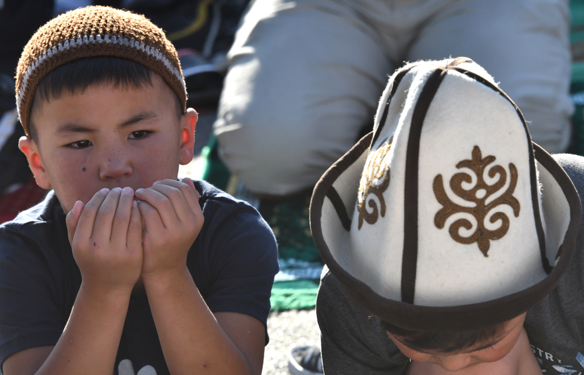 Young Kyrgyz Muslims pray on the first day of the Eid al-Adha in central Bishkek, Kyrgyzstan [Vyacheslav Oseledko/AFP]