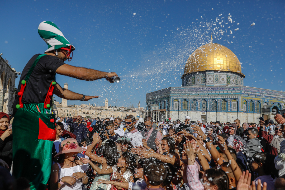 Palestinians celebrate the first day of Eid al-Adha near the Dome of Rock mosque at the Al-Aqsa Mosque compound, Islam's third holiest site, in the Old City of Jerusalem [Ahmad Gharabli/AFP]