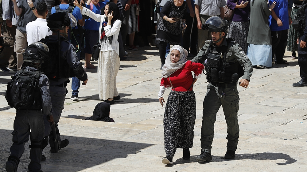 A member of the Israeli security forces restrains a Palestinian girl during clashes that broke out at the al-Aqsa Mosque compound in the Old City of Jerusalem on August 11, 2019, during the overlappin