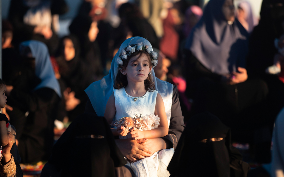 A Palestinian girl attends prayers to mark the first day of Eid al-Adha in Gaza City [Khalil Hamra/AP Photo]