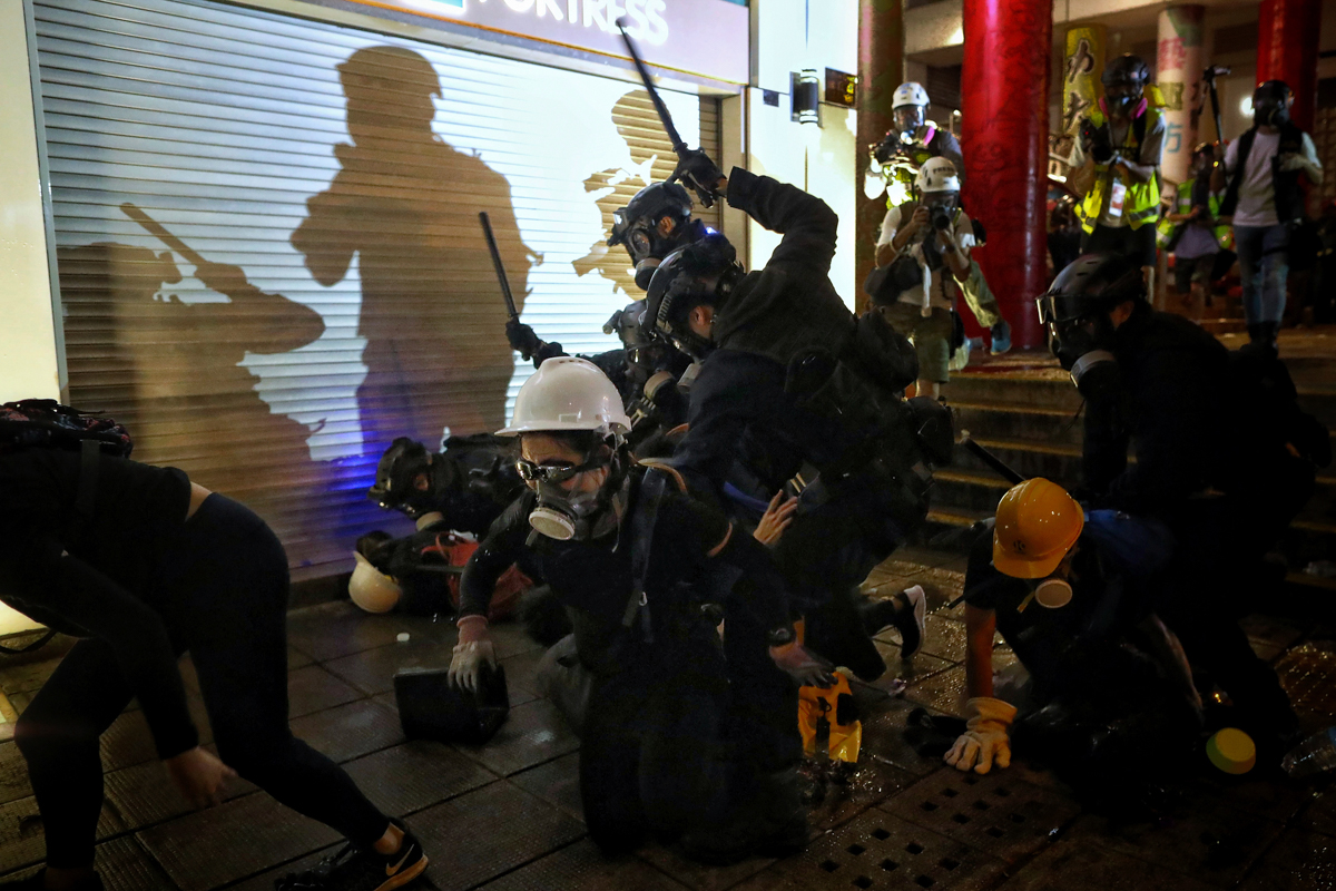 Police charge at protesters in front of Tsim Sha Tsui police station. [Eric Tsang/HK01 via AP]