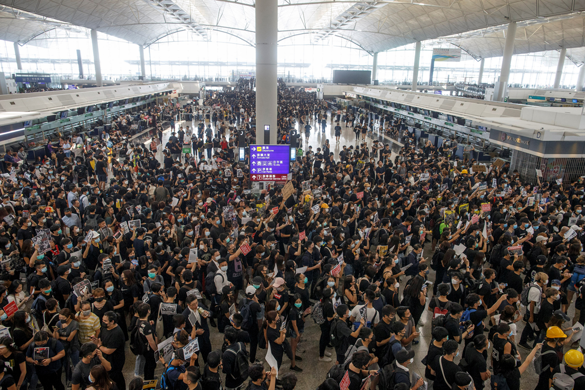 Thousands of pro-democracy protesters flooded the city's airport to denounce police violence. [Thomas Peter/Reuters]
