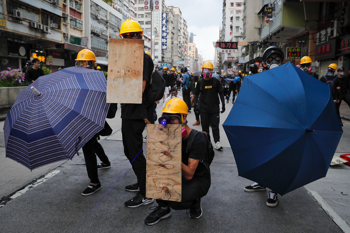 Protesters with umbrellas and homemade shields prepare to face riot police. [Kin Cheung/AP Photo]