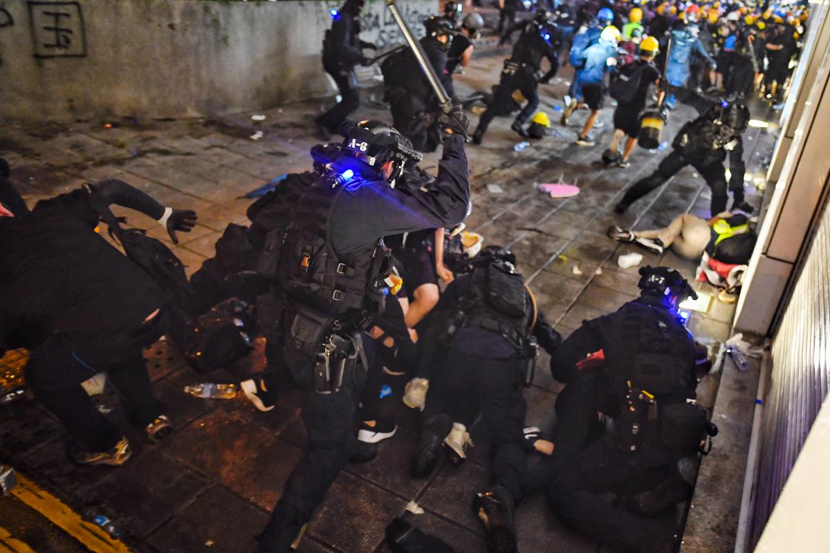 Police disperse protesters outside Tsim Sha Tsui police station. [Manan Vatsyayana/AFP]