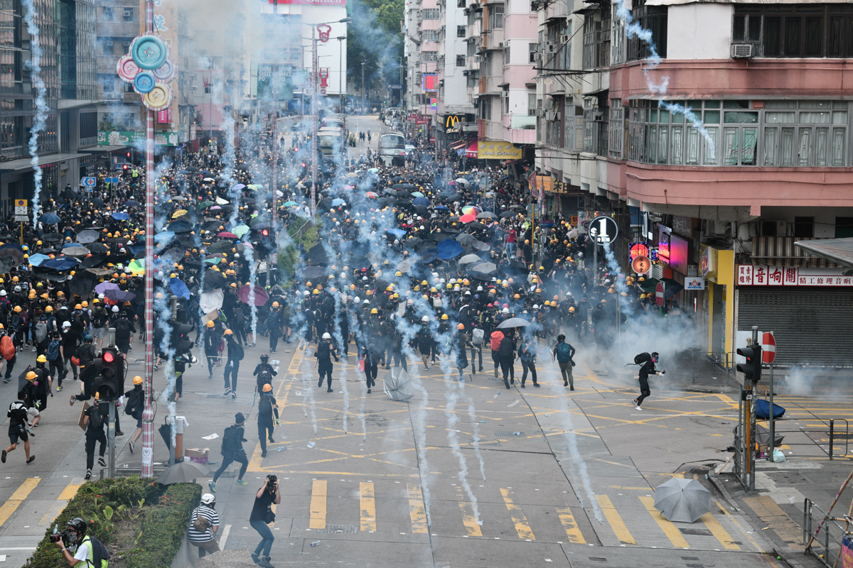 Pro-democracy protesters throw back tear gas canisters fired by the police during protests in the Sham Shui Po district. [Anthony Wallace/AFP]