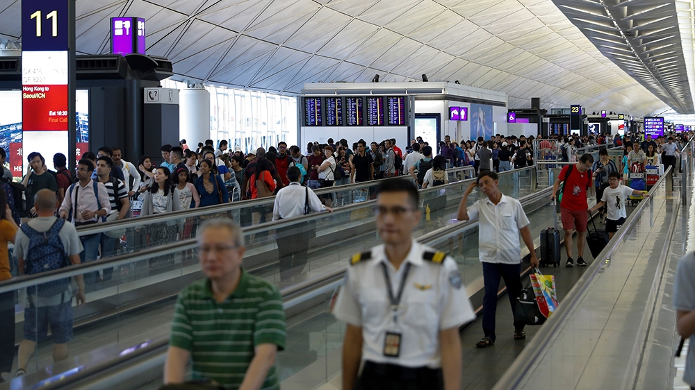 Traveller walk at the departure hall as flights information boards displaying numerous flights was cancel ay the Hong Kong International airport, Monday, Aug. 12, 2019. One of the world's busiest airp