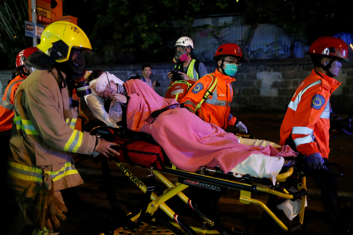 An injured protester receives medical assistance in Tsim Sha Tsui neighbourhood. [Issei Kato/Reuters]