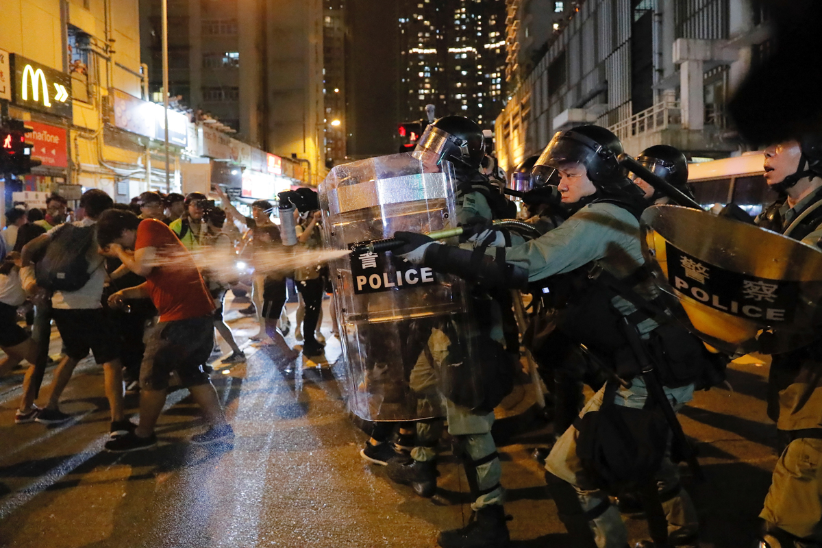 Riot police use pepper spray against protesters. [Kin Cheung/AP Photo]