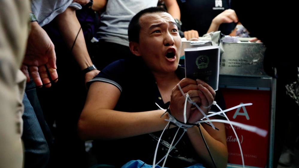 Fu Guohao, reporter of Chinese media Global Times website, is tied by protesters during a mass demonstration at the Hong Kong international airport, in Hong Kong