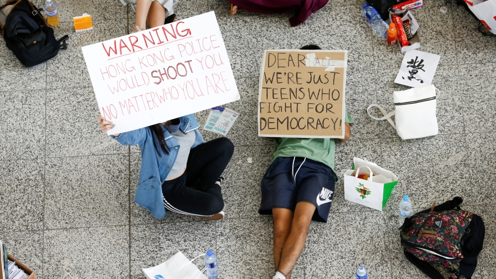 Anti-government demonstrators sit in a designated area of the arrival hall of the airport in Hong Kong after police and protesters clashed the previous night