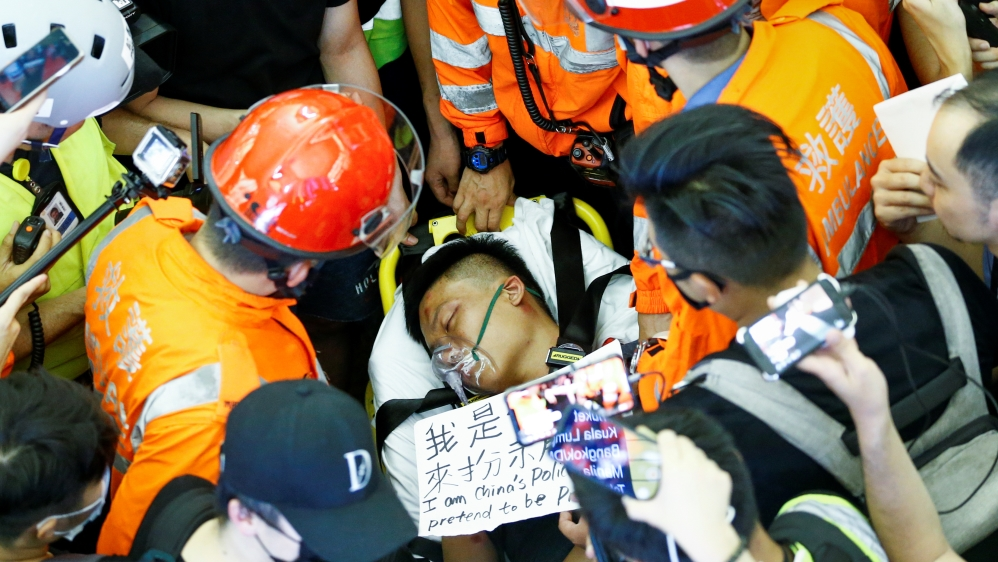 Doctors try to remove an injured man, who some anti-government protesters said was an undercover police officer from China, at Hong Kong airport